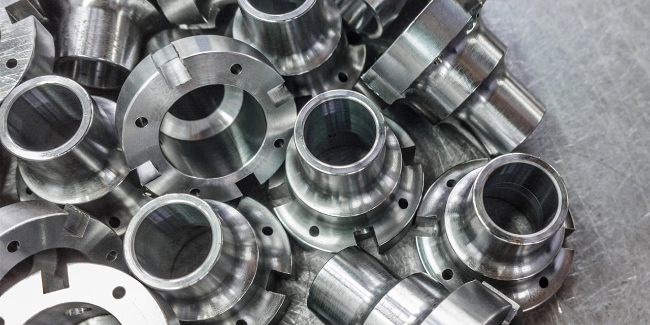 denatec-shiny-steel-parts-after-cnc-turning-drilling-and-machining-on-steel-surface-selective-focus-close